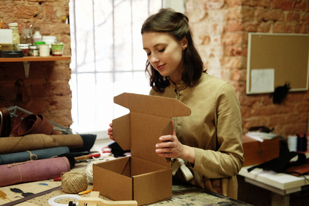 woman folds packing box in sewing workshop