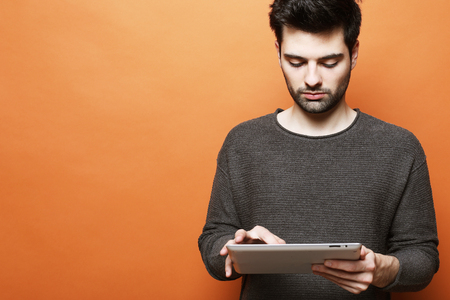 Serious young bearded man using digital tablet against orange background Imagens