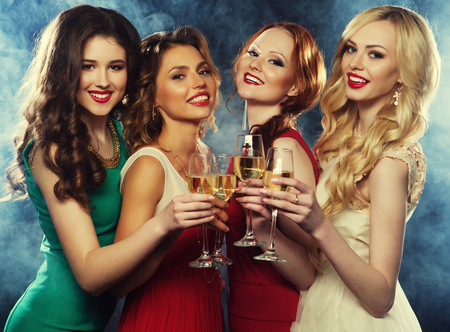 lifestyle, party and people concept - Group of partying girls wearing dress, with sparkling wine Stock Photo