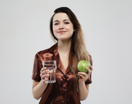 beautiful girl dressed in pajamas holding a green apple and a glass of water