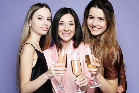 three beautiful girls dressed in pajamas drink champagne and have fun
