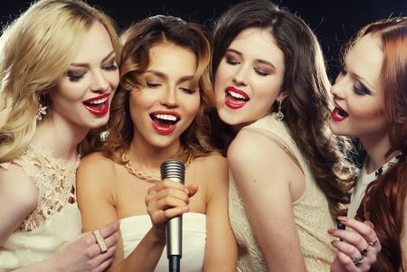 Lifestyle-, Party- und People-Konzept - vier schöne, stilvolle Mädchen, die Karaoke im Club singen Standard-Bild