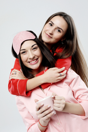 two beautiful girls dressed in pajamas hugging and taking selfies