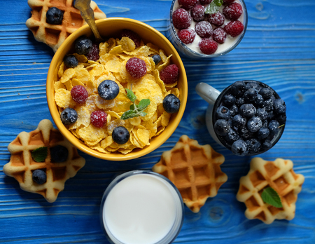 Healthy breakfast. Corn flakes with raspberries and blueberries, granola with yogurt and berries, wafers and milk. A great start to the day. Top view. Close up. Imagens