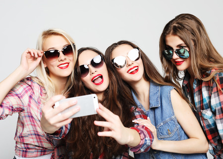 four happy teenage girls with smartphone taking selfie
