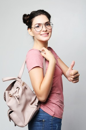 young brunette woman wearing a pink t-shirt and jeans is holding a backpack and smiling Stock Photo