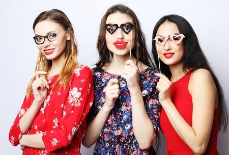 giovani donne in possesso di bastoncini di carta per feste su sfondo bianco