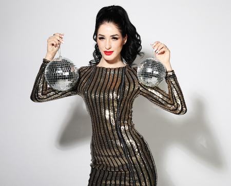 lifestyle, party and people concept - Happy smiling woman in amazing evening dress holding disco balls Stock Photo