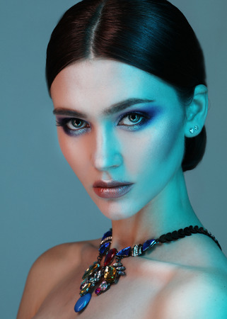 High Fashion model woman posing in studio. Portrait of beautiful sexy girl wearing jewelry with trendy make-up Stock Photo - 124758256