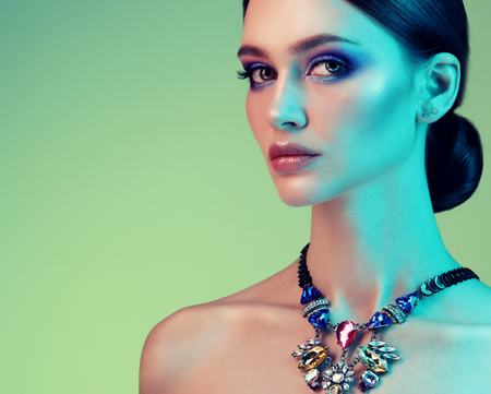 High Fashion model woman posing in studio. Portrait of beautiful sexy girl wearing jewelry with trendy make-up Stock Photo - 124758258