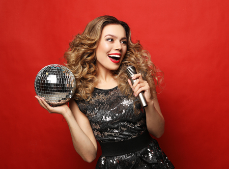 lifestyle, party and people concept - woman in evening dress holding microphone and disco ball