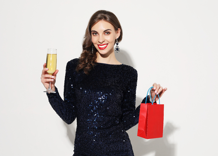 Portrait of an young beautiful girl wearing evening dress and holding shopping bag