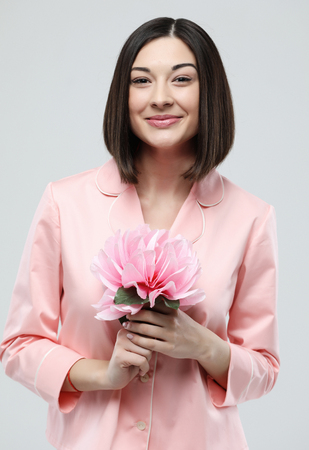 beautiful girl dressed in pink pajamas holding pink flower over white background