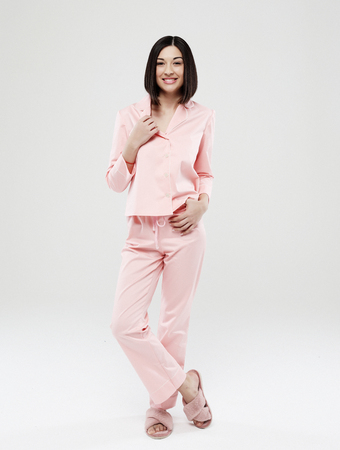 lifestyle, fashion, and people concept - beautiful brunette girl dressed in pink pajamas over white background Stock Photo