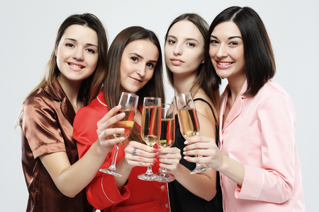 four beautiful girls dressed in pajamas drink champagne and have fun