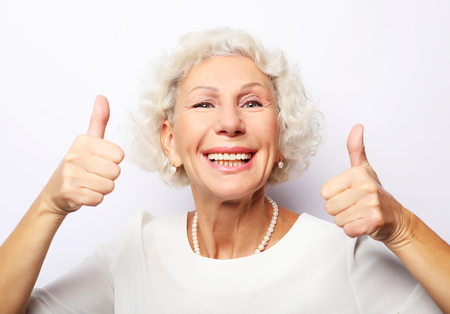 Lifestyle, emotion and people concept: Elderly happy woman giving a thumb up and looking at the camera Stock Photo