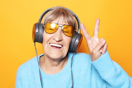 Musica d'ascolto della signora anziana divertente e che mostra i pollici in su.