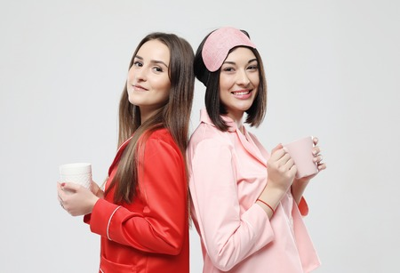 two beautiful girls dressed in pajamas hugging and holding cups