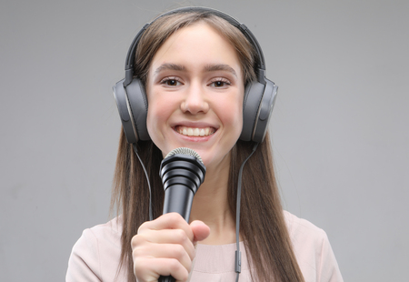 Expressive girl singing with a microphone and headphones Reklamní fotografie