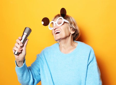 lifestyle, people and party concept: happy old woman with big eyeglasses holding a microphone and singing Reklamní fotografie