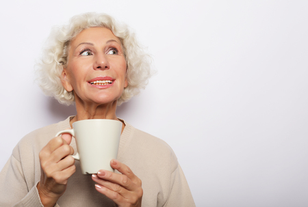 old excited lady smiling laughing, holding cup drinking coffee, tea, over white background Banque d'images - 124767773
