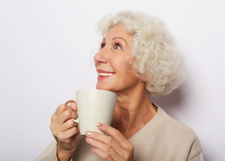old excited lady smiling laughing, holding cup drinking coffee, tea, over white background Banque d'images - 124767774