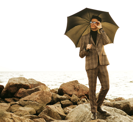fashionable young man with umbrella standing near the sea Banco de Imagens