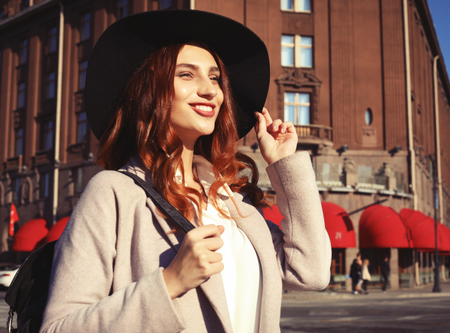 Outdoor portrait of yong beautiful happy smiling woman wearing stylish hat, coat. Stock Photo