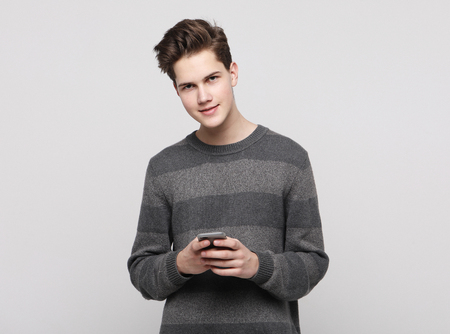 Happy young man typing sms on white background