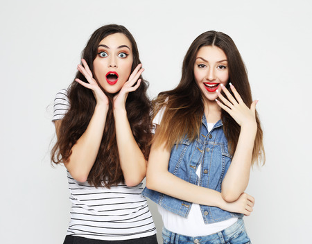 Two young girl friends having fun. Both making surprised faces. Stockfoto