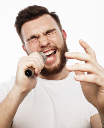 young bearded man in white shirt singing in microphone Stock Photo