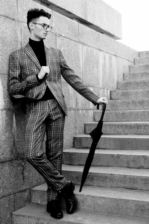 fashionable young man in glasses with umbrella standing on the stairs