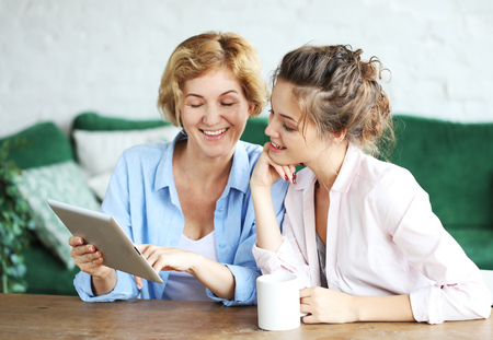 lifestyle, technology and people concept: mother and adult daughter using tablet computer at home