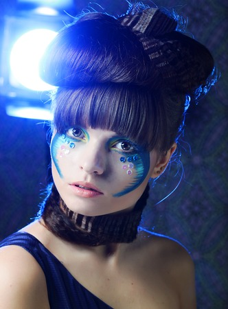 brunette with creative make up in blue dress