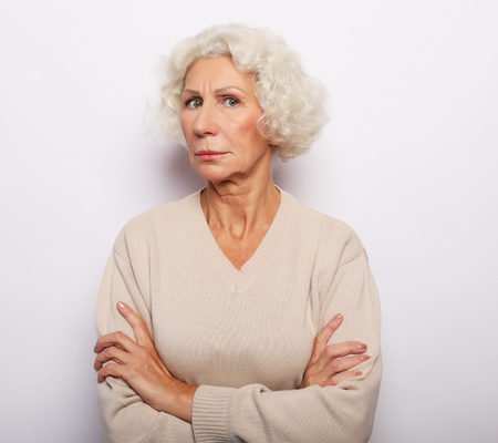 Portrait of confident elderly woman looking at camera with arms crossed on chest