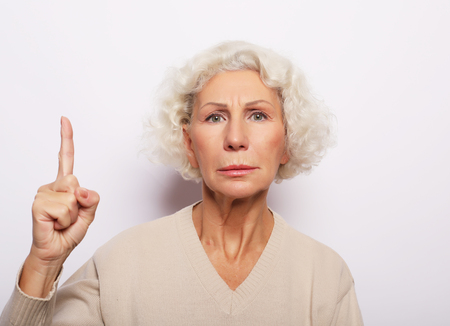 idea, attention and people concept - portrait of smiling senior woman pointing finger up over white background