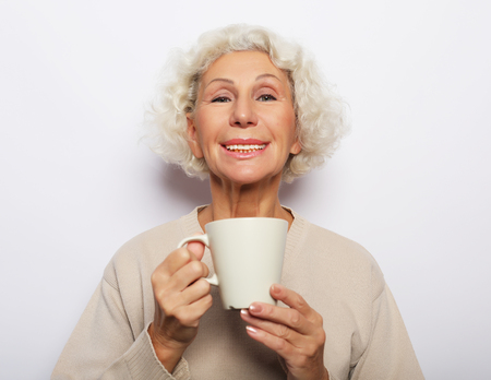 old excited lady smiling laughing, holding cup drinking coffee, tea, over white background