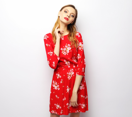 Young beautiful woman wearing red dress posing over white background