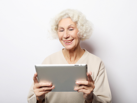 lifestyle, technology and people concept: Happy mature woman using a tablet Stock Photo