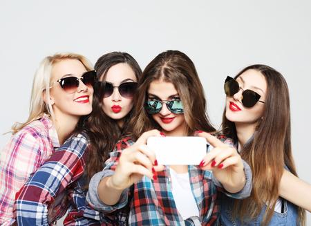 happy teenage girls with smartphone taking selfie