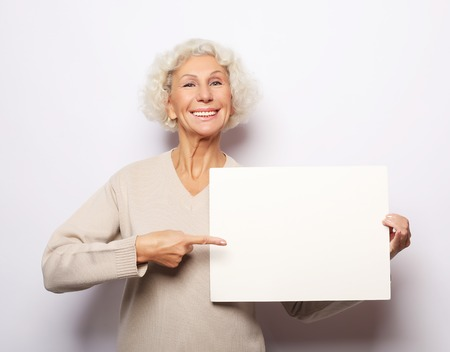 Aged woman with blank advertising board or copy space. Portrait of handsome expressive grandmother in lightbeige sweater. Indoor,studio shot, isolated on white background