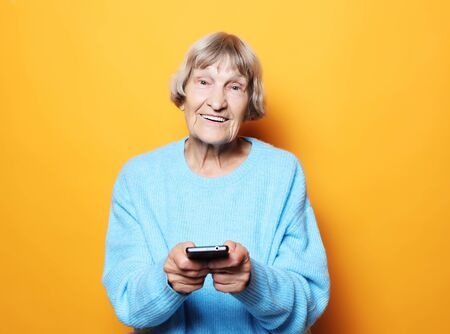 old woman wearing blue sweater  talking on cell phone