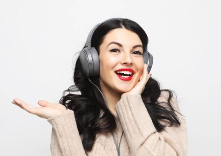 surprised and attractive woman in beige sweater with headphones