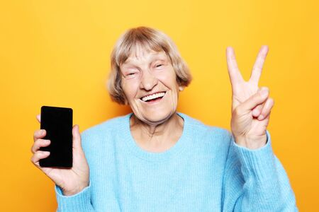 lifestyle, tehnology  and people concept: Elderly lady holding  a smartphone making v-sign