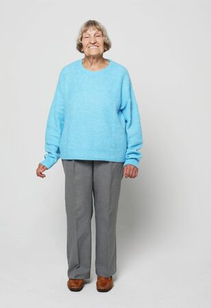 Full length portrait of a content senior lady smiling and looking at the camera Stock Photo