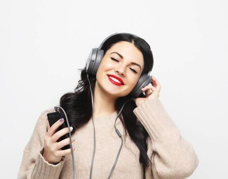 young curvy brunette woman in headphones listening to music
