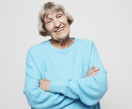 portrait of a content senior lady wearing blue sweater smiling and looking at the camera Stock Photo