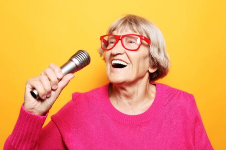 Portrait of funny grandmother holds up the microphone stand and sings isolated on vivid yellow background Banco de Imagens