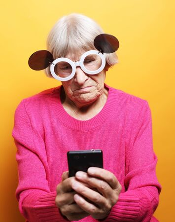 lifestyle, tehnology and people concept: Elderly lady holding a smartphone