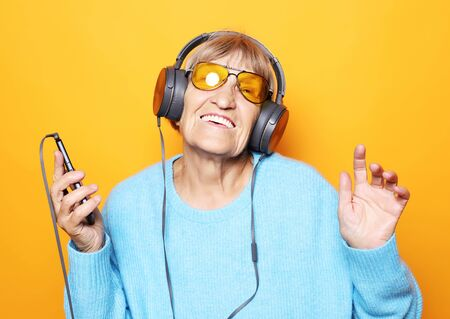 senior woman listening to music with smartphone isolated on yellow background